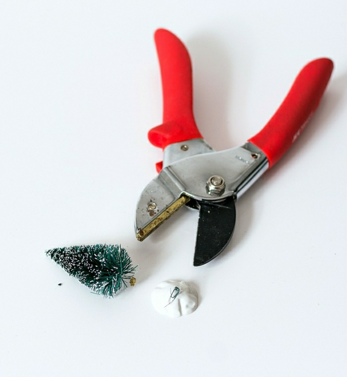 diy gift ideas, pair of metal pliers with red plastic handles, a small snowy Xmas tree ornament, a white plastic stand, white background