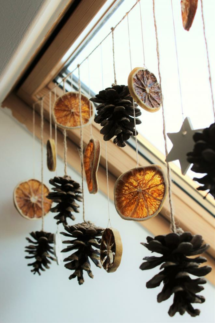 dried orange slices, several pine cones and star shapes, tied to a string and hanging from a ceiling window with wooden window pane