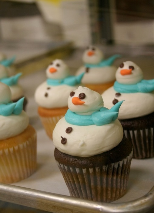 batch of vanilla and chocolate cupcakes, decorated with white marshmallow frosting, shaped like snowman, with pale blue scarf, orange nose and chocolate details