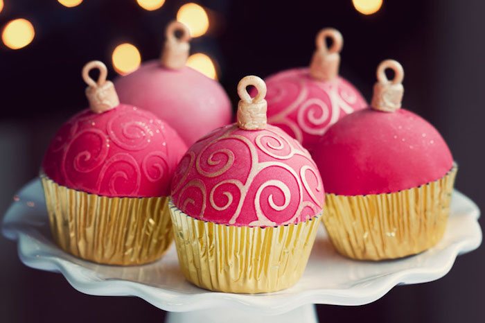 five cupcakes in golden wrappers, with pink fondant icing made to look like christmas tree ornaments, white dish on dark background