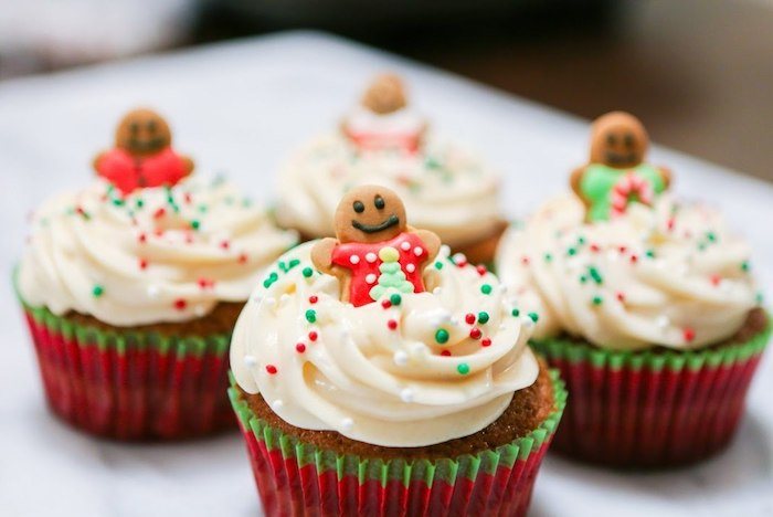 four cupcakes in red and green wrappers, with creamy white icing, decorated with small gingerbread men, and red and green sprinkles