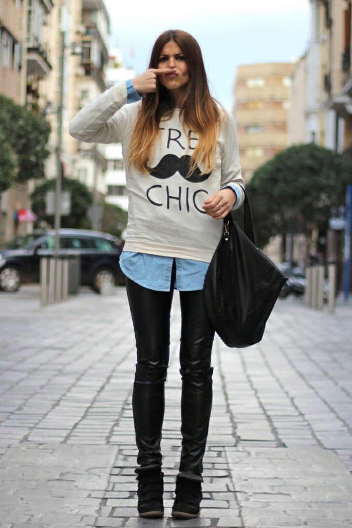 casual business attire, funny photo of young woman, with skinny black leather trousers, denim shirt under white top with black print, black bag and shoes