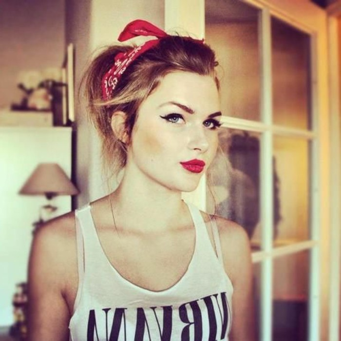 young woman with pinup make up, red lipstick fake lashes and eyeliner, hair tied back with red and white bandanna, wearing white tank top with black writing