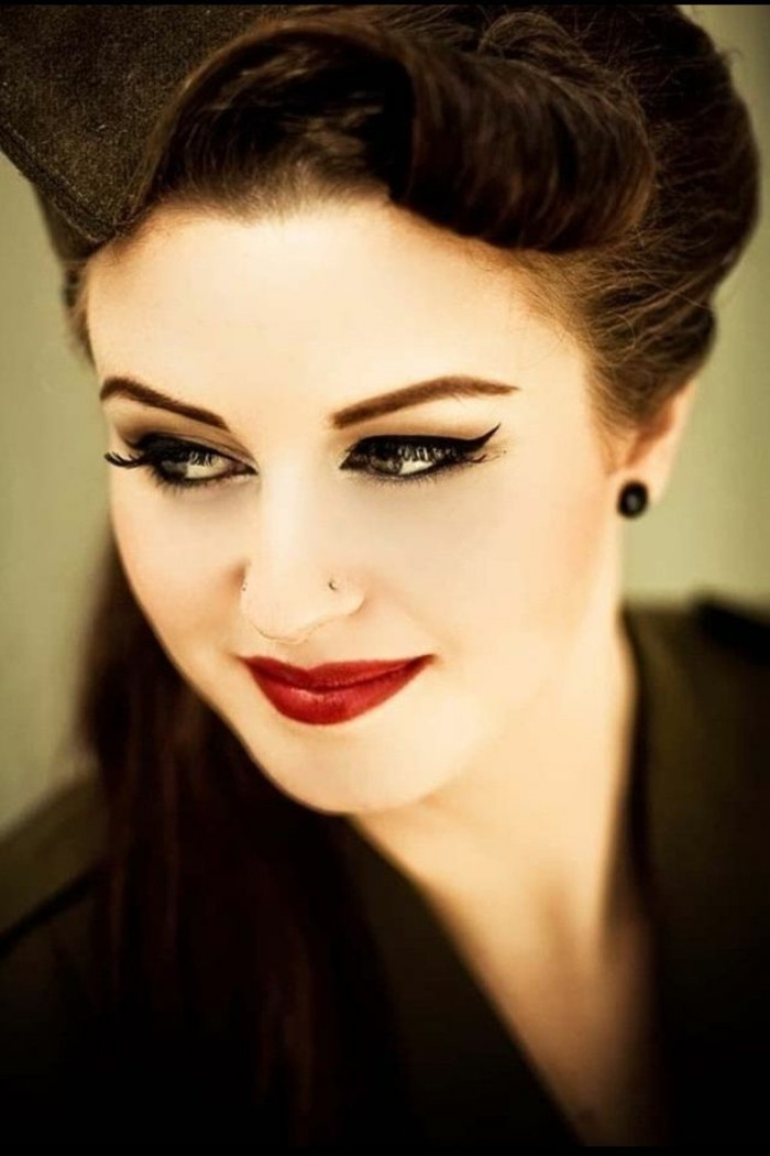dark-haired smiling woman, deep red lipstick and fake lashes, mascara eyeliner and penciled eyebrows, black earring and black top, nose ring and vintage hairstyle
