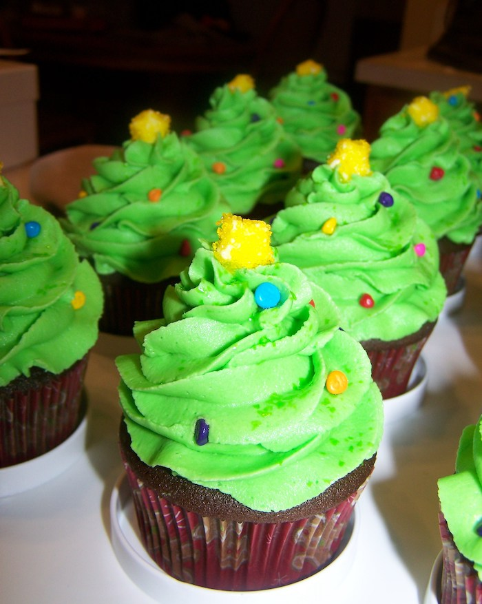 chocolate cupcakes images, batch of chocolate cupcakes, with bright green frosting shaped like x-mas tree, decorated with colorful sprinkles, and small yellow candy stars