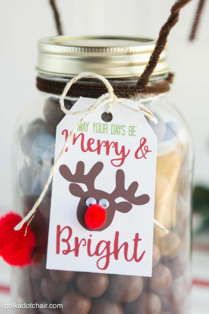 family christmas gifts, close up of clear jar with screw-top lid, with a white label featuring a reindeer drawing and a festive message tied to it with string, red pom poms and brown wire antlers