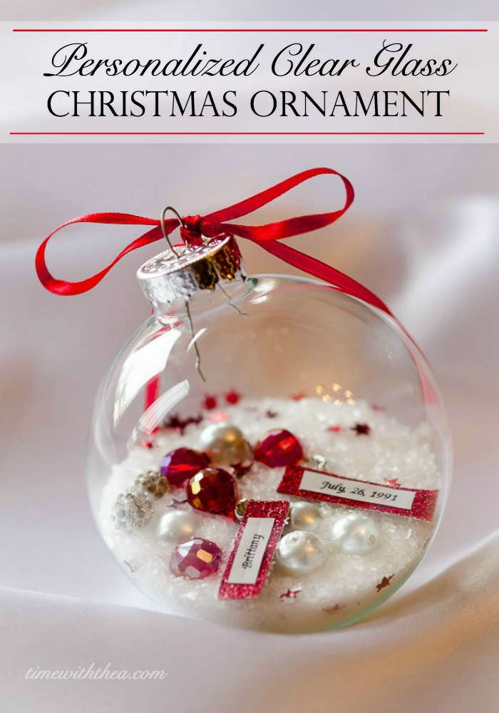 cheap christmas gift ideas, clear glass christmas bauble, filled with white glitter, fake pearls and red jewels, and pieces of paper with writing, silver cap tied with a red ribbon