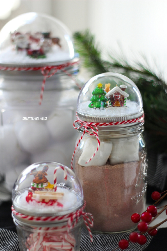 diy gift ideas, three differently sized mason jars, close up of small jar filled with candy, topped with snow globe, bigger jar full of cocoa and marshmallows, bigger jar blurred in background