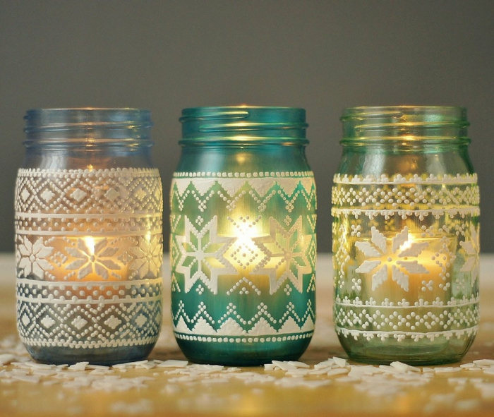 xmas gifts, three white, light blue and yellow mason jars with candles inside, decorated with white 3D drawing,featuring a nordic knit pattern,