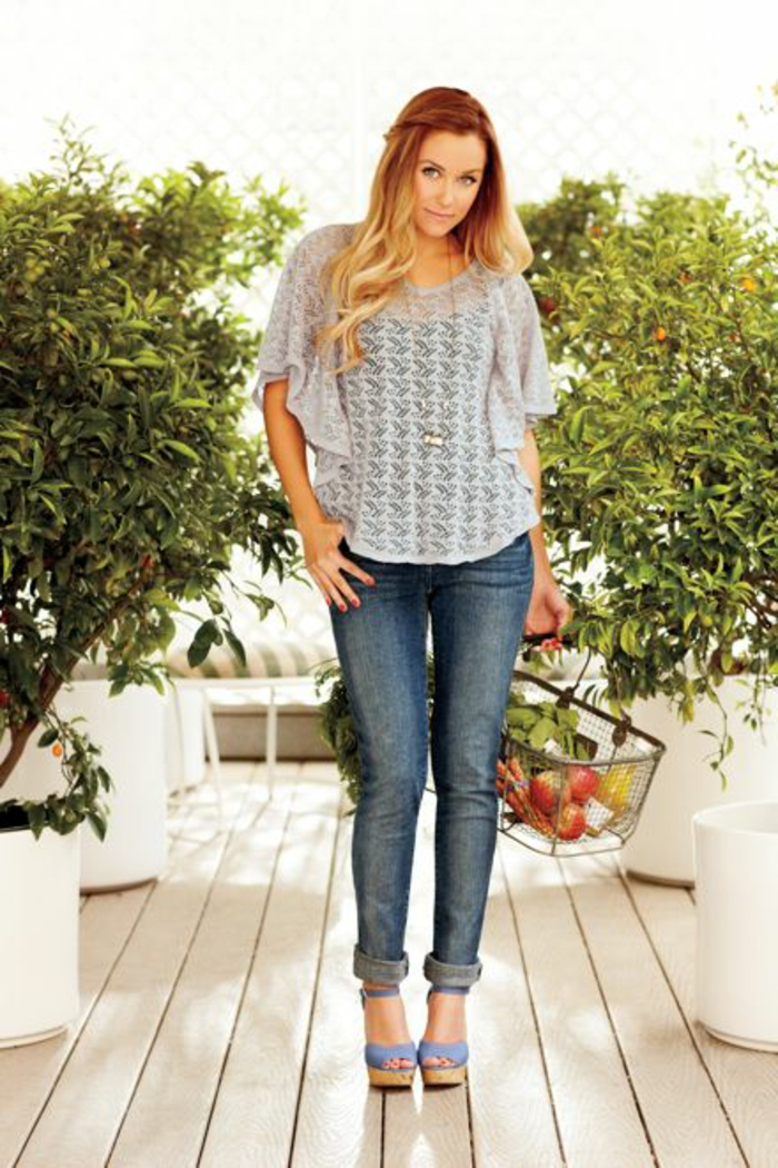 casual business attire, honey blond woman with long wavy hair, wearing sheer lace top with butterfly sleeves over black top, blue jeans and blue chunky-heeled sandals