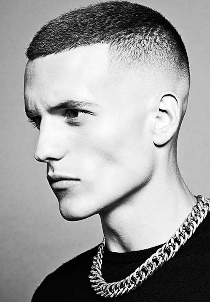 faded undercut, black and white photo of slim young man with serious repression, dark top and chunky metal chain around neck, short hair cropped even shorter on the side