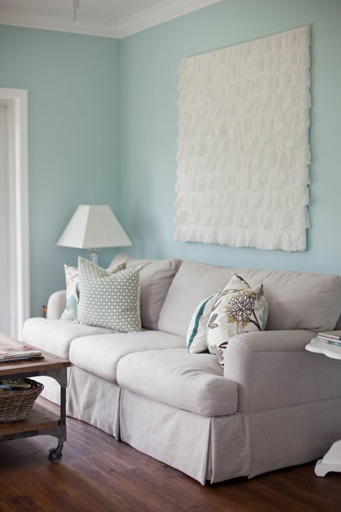 pale pastel blue wall, white ceiling plaster details and big square ruffled fabric ornament, pale grey couch with colorful cushions, white lamp and wooden table