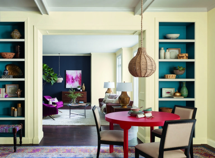 paint colors for living room, pale yellow rooms with white ceilings and dark blue details, red round table, three brown and cream chairs, colorful carpet and dark wooden floor, in-built display shelves
