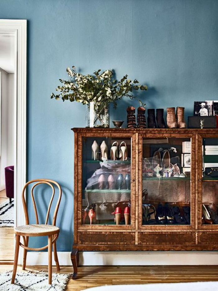blue wall with white door frame, brown display cabinet containing many shoes, wooden chair and floors, glass vase with green plants, pale grey rug