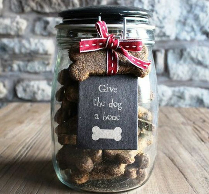 christmas crafts for adults, a clear jar with snap closure and black lid, containing homemade dog biscuits shaped like bones, one bone biscuit tied to closure with red and white ribbon, black label