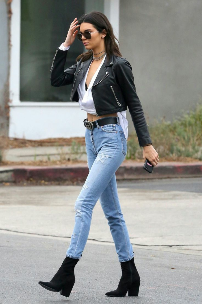 kylie jenner wearing white crop top, skinny jeans with black belt and black ankle-boots, black cropped leather biker jacket and sunglasses