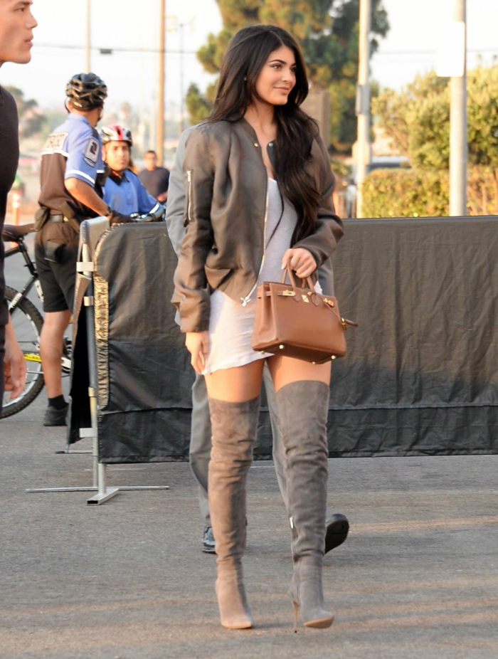 business casual dresses, kylie jenner wearing white mini dress, thigh-high grey boots with high heels, grey leather bomber jacket, holding small brown bag