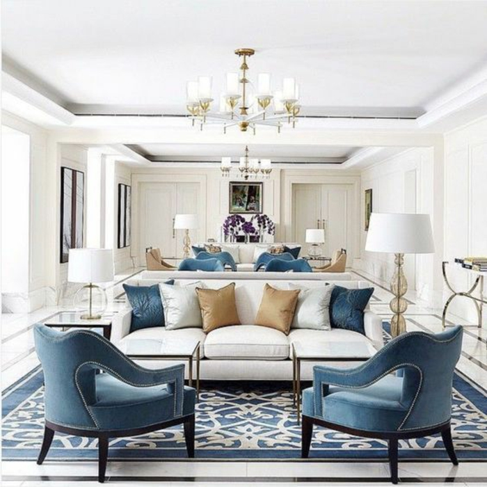 big room with white sofas, blue white and pale brown cushions, blue chairs with black legs, blue and white colored carpet, white lamps and chandeliers