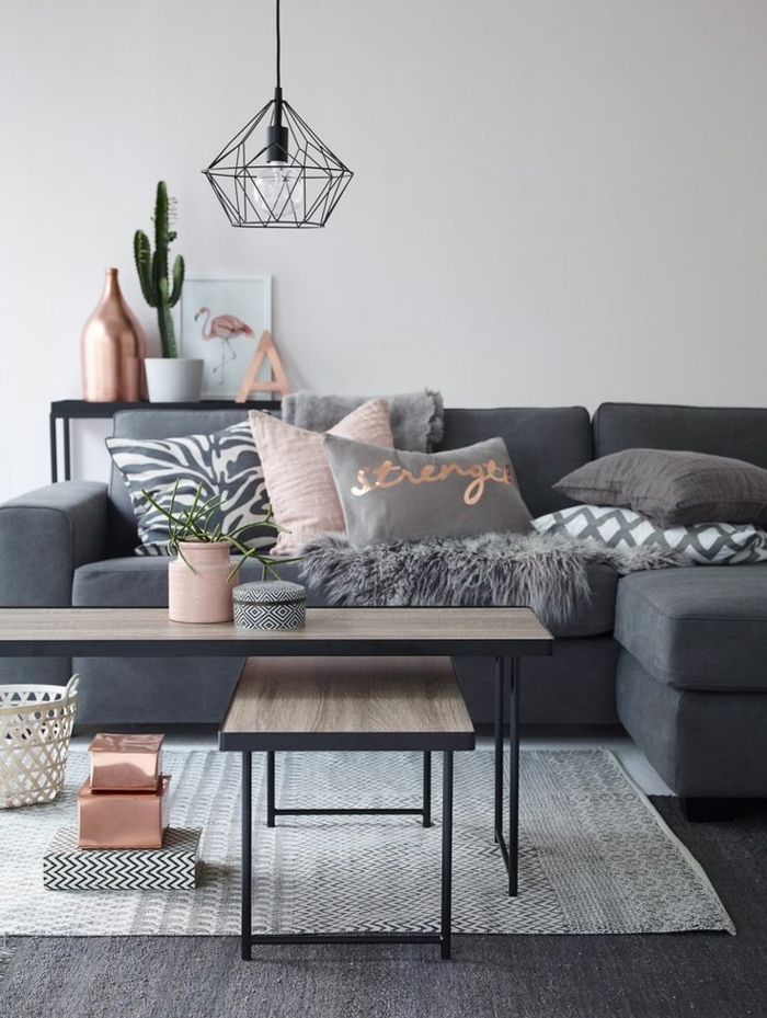 neutral colors, pale grey wall and dark grey sofa with pillows in pink, grey and white, two pale wooden tables with black metal legs, black metal lamp and light grey rug