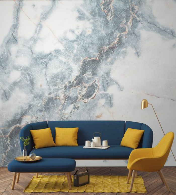 interior painting, marble colored grey and white wallpaper, dark blue sofa with three yellow cushions, yellow chair and rug, dark blue table with gold trey, old radio and wooden floor