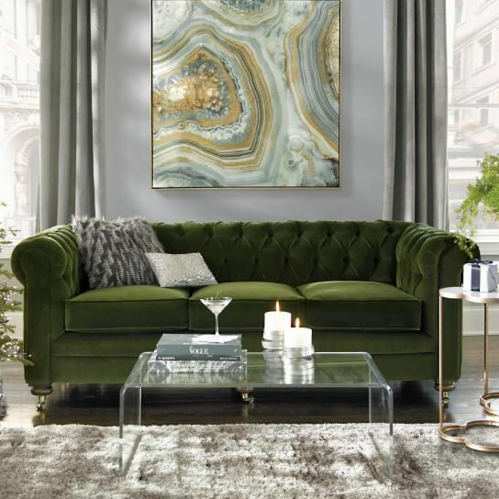 Lush Green Sofa With Two Grey Cushions, Clear Glass Table With Two Lit  Candles,