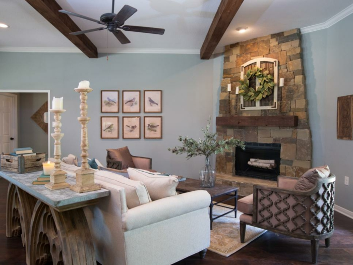 color schemes for living rooms, room with white ceiling, wooden beams and a ceiling fan, white sofa and two brown chairs, dark wooden table and brown stone fireplace