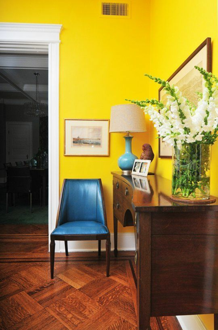 living room paint colors, bright yellow wall with white door frame, saturated blue chair and blue and cream lamp, brown wooden chest of drawers, wooden floor and big clear vase with white flowers
