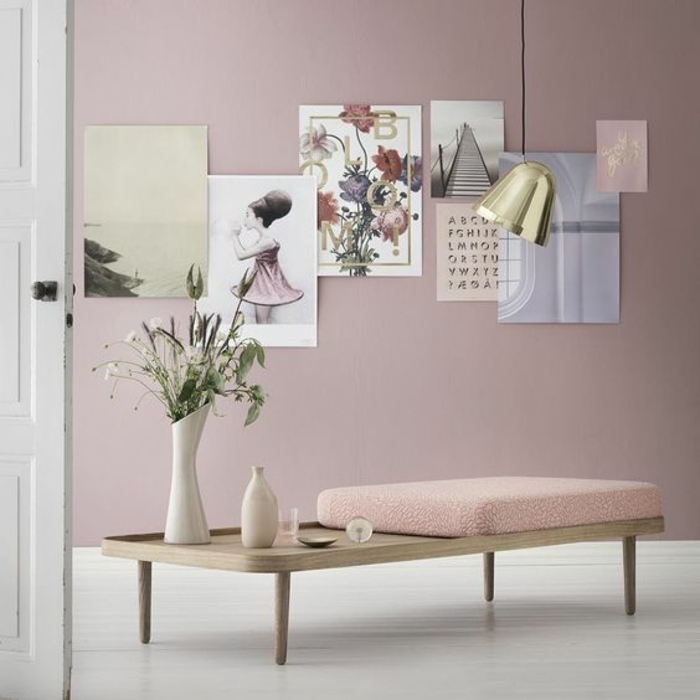color schemes for living rooms, white open door, light wooden table with pink cushion short legs, pink wall with seven colorful posters, white floor vase and decorative bottle