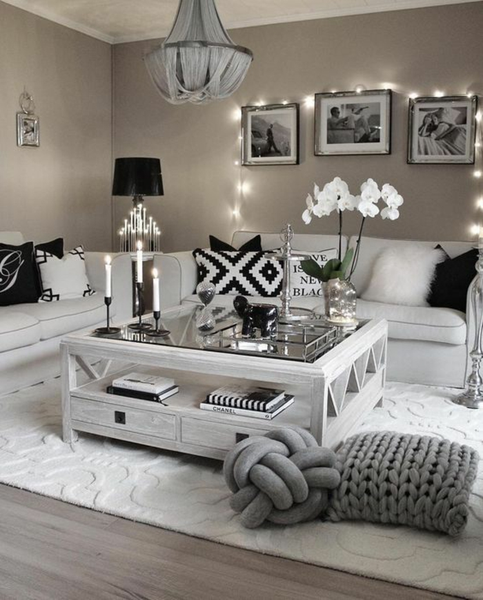 mink-colored walls, two off-white sofas with black and white cushions, white wooden table with glass top, wooden floor and white carpet, three framed images and fairy lights