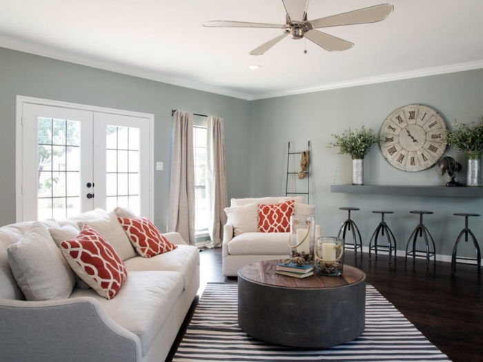 color schemes for living rooms, spacious room with white ceiling, white sofa and chair, three orange and white cushions, duck's egg colored walls, big wall clock and round coffee table