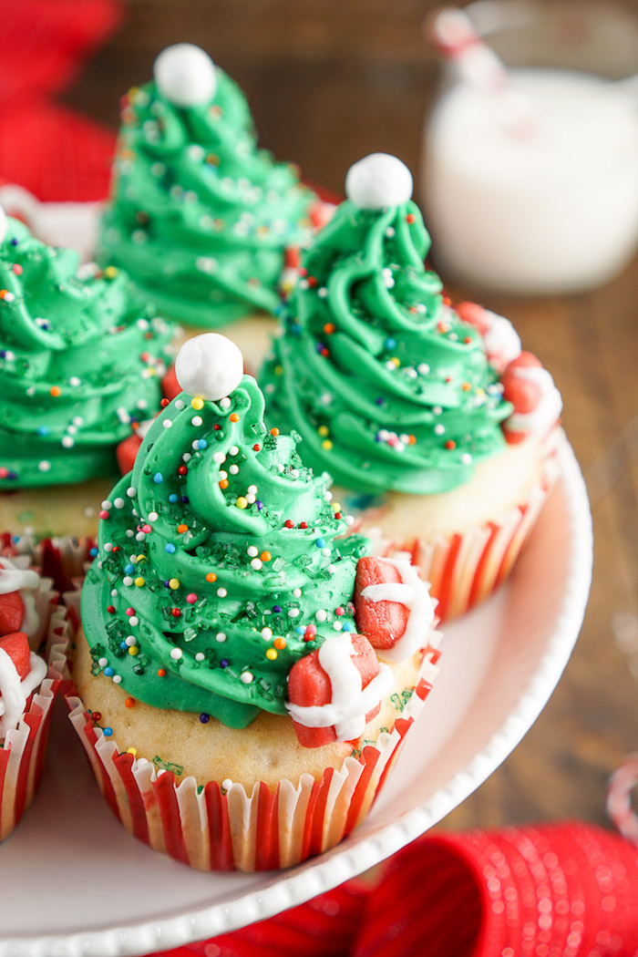 christmas baking ideas, several pale yellow cupcakes, with green frosting made to look like christmas tree, colorful sprinkles white pearls and fondant presents