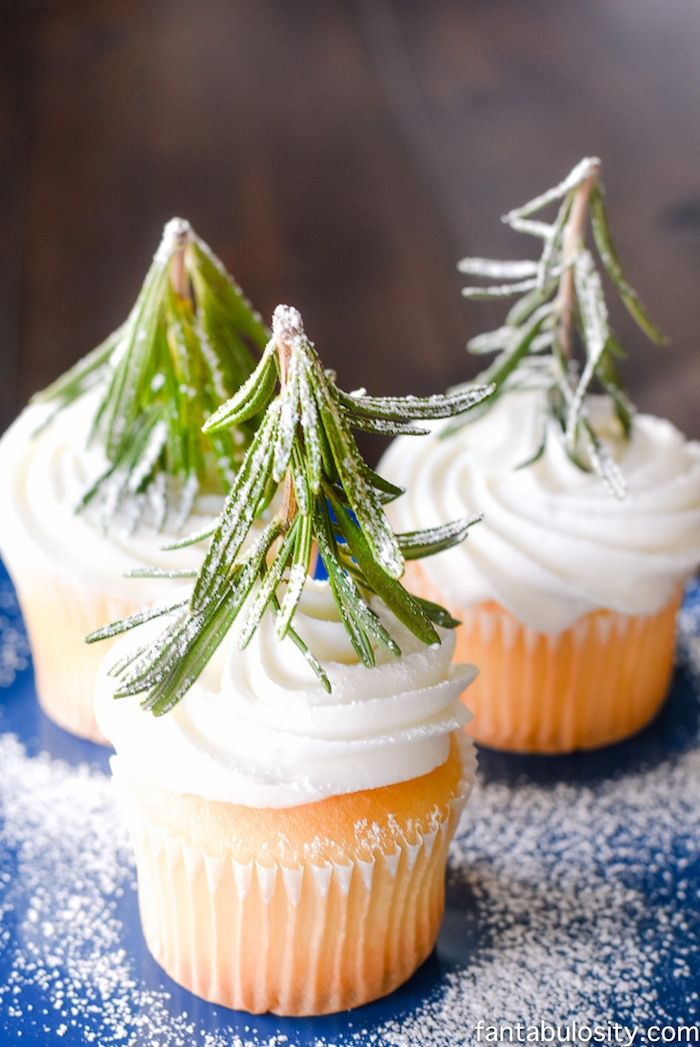 christmas flavors, three vanilla cupcakes with creamy white icing, each decorated with rosemary stalk and dusted with powdered sugar