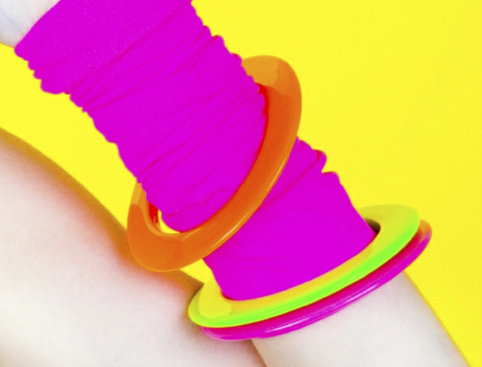 close up of arm with a neon pink arm-warmer, neon orange yellow and pink bangles, acid yellow background