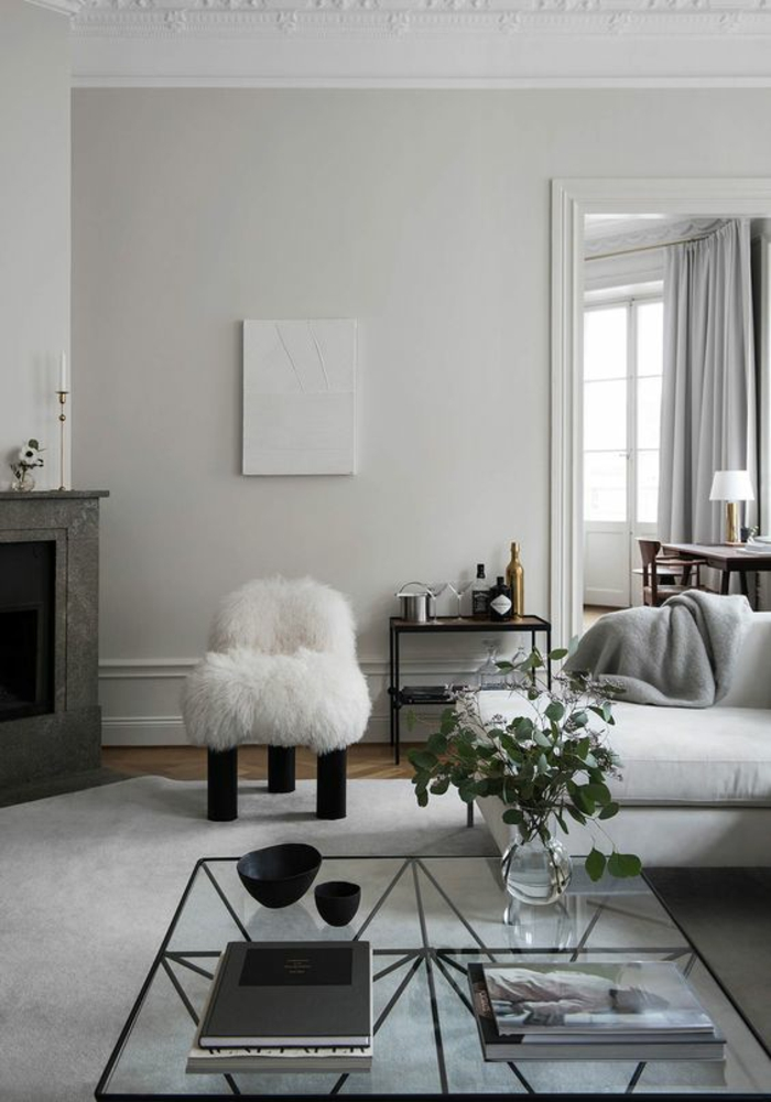 living room color schemes, white and pale grey room, dark grey fireplace, white fluffy chair with black legs, white sofa with grey blanket, clear glass table with black metal details