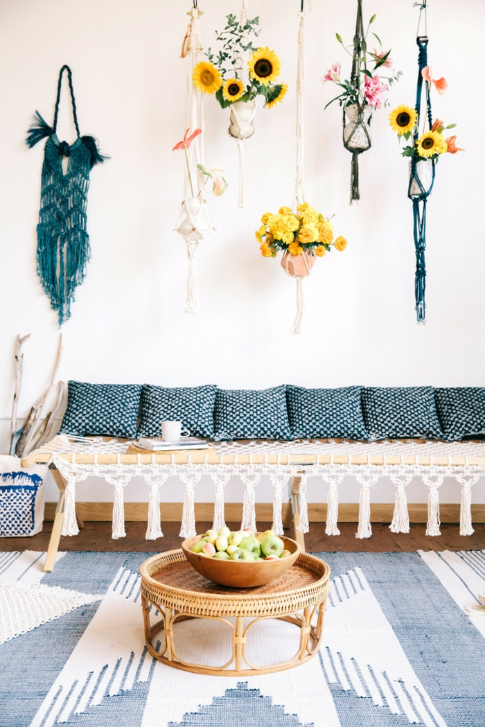 neutral colors, cream wall hung with blue and cream woven holders containing flowers, light wooden bench with white woven cover, six blue and white pillows, round oriental bamboo table, white and blue carpet
