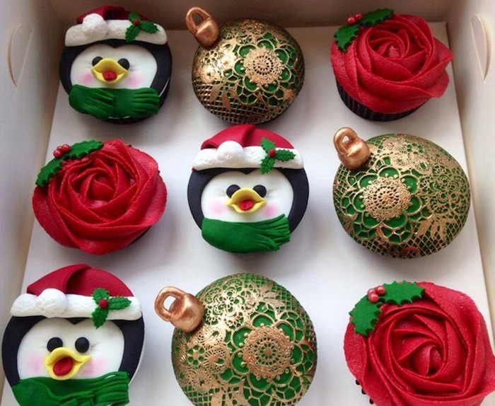 nine cupcakes in white box, three with red icing made to look like a rose, three with colorful icing made to look like penguin, three with green and gold icing made to look like ornaments