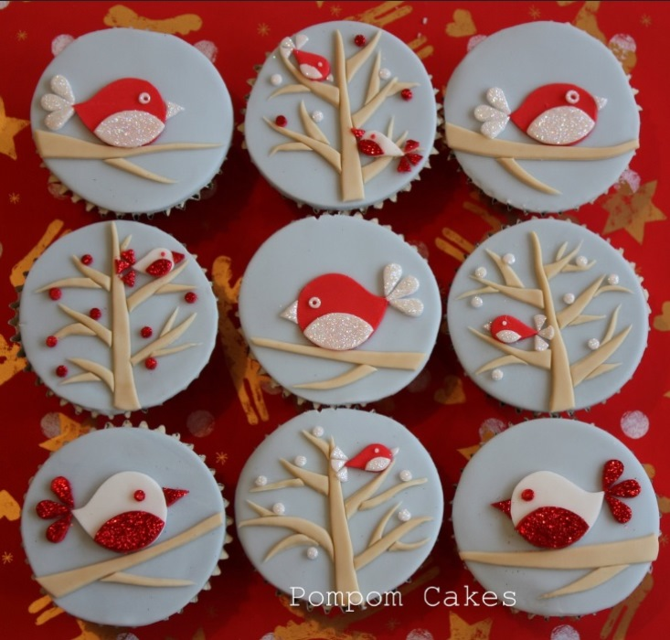 christmas baking ideas, nine cupcakes with pale blue fondant icing, decorated with brown, sparkly red and white fondant birds and trees