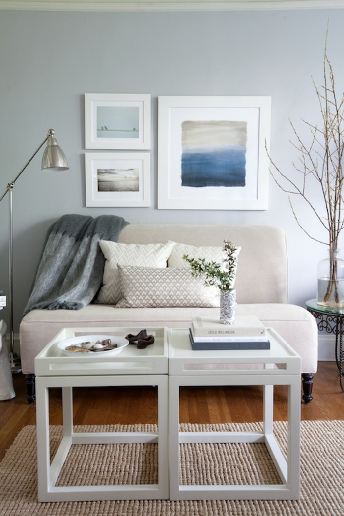 pale blue wall with three images in white frames, pale cream sofa with grey blanket and three pillows, small white table, wooden floor and cream rug
