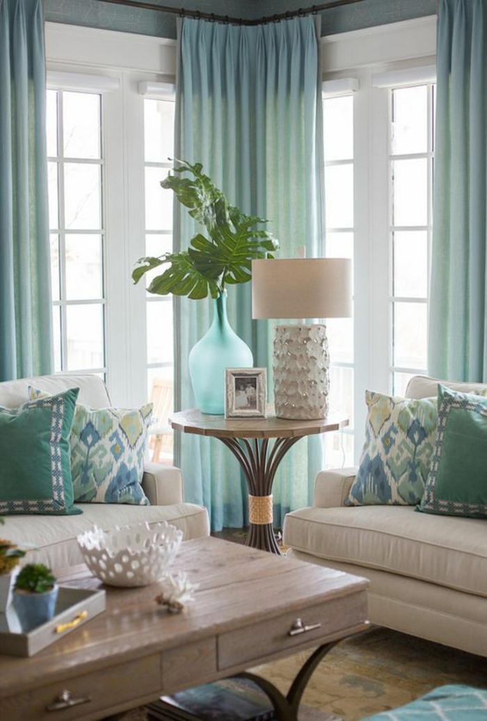 windows with white frames and light blue curtains, two cream colored sofas with blue cushions, light colored wooden table with drawers, round coffee table with blue vase with green plant