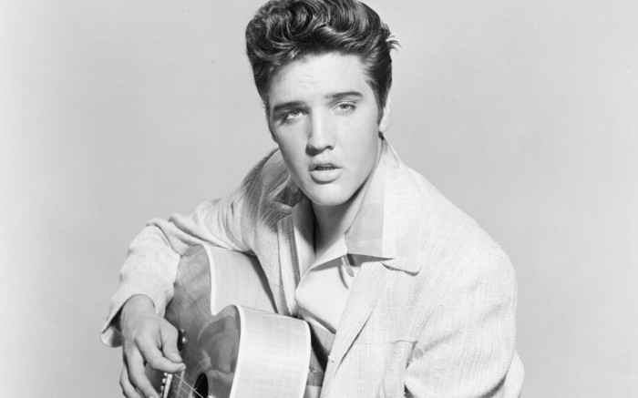 black and white photo of elvis presley, pale blazer and shirt, wavy messy gelled up hair, holding acoustic guitar, playing and singing