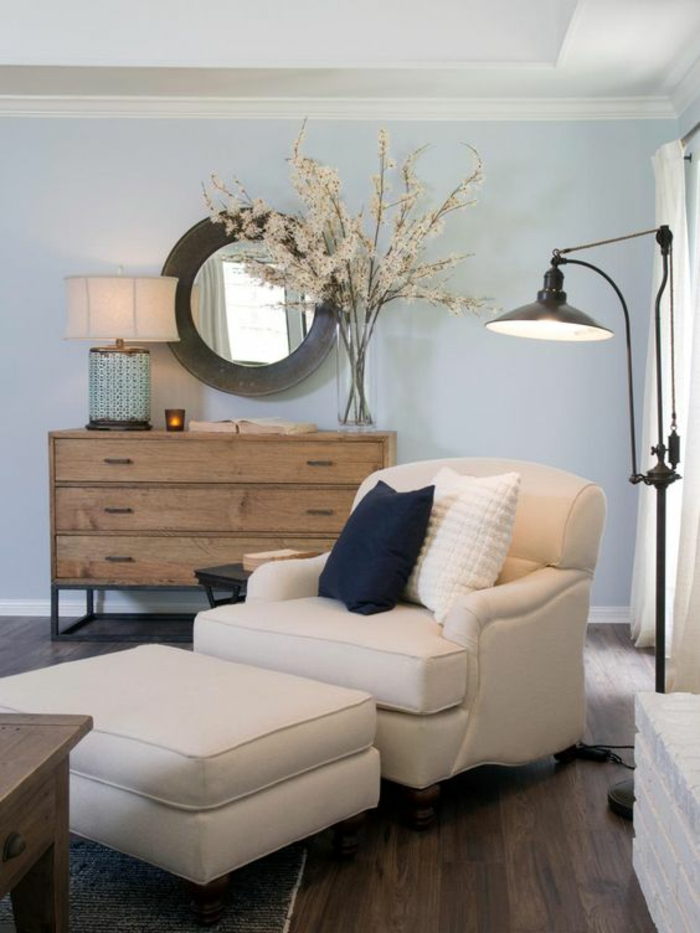 dark wooden floor, cream seat with ottoman, black and white pillows, brown wooden chest of drawers, round mirror with big wooden frame, black lamp and class vase with white flowers