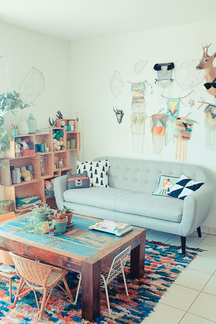 living room color schemes, cool pale green room with very pale blue sofa, shabby massive wooden table, colorful rug and different chairs, floor tiles display cabinets and ornaments