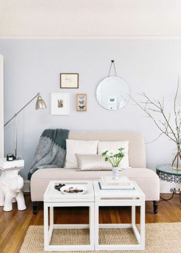 two tone living room walls, pale lilac and cream wall, very pale small pastel pink sofa with three cushions, small white coffee table, wooden floor and cream rug, lamp framed images and grey blanket