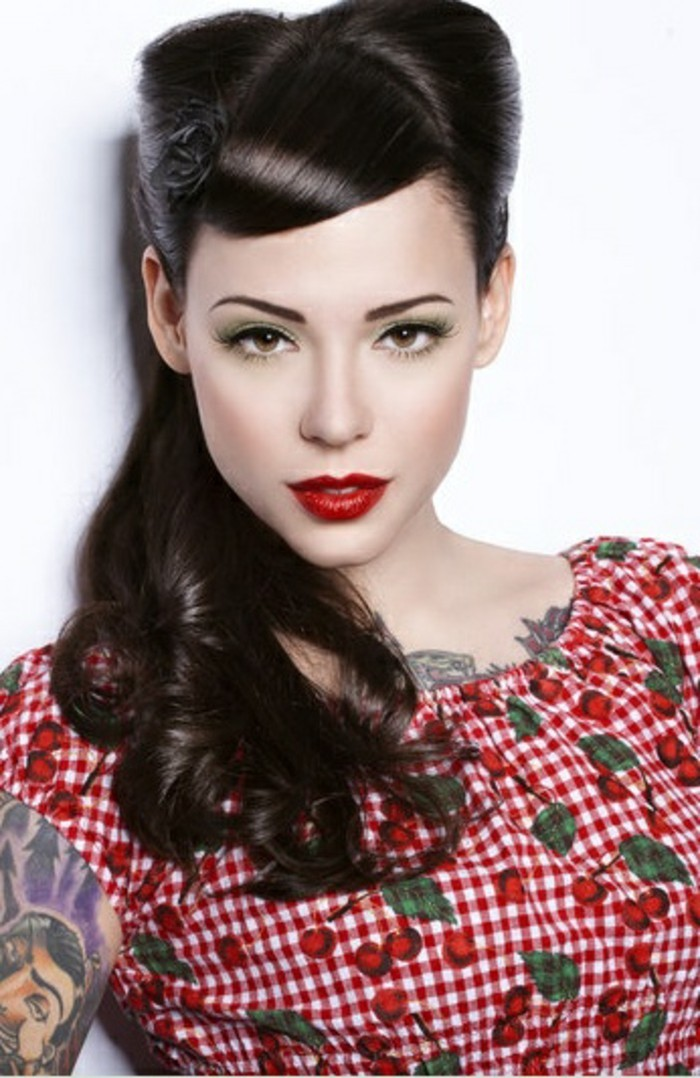 woman dressed and made up in rockabilly style, dark mid-length hair with curls, side bangs and victory rolls, bright red lipstick tattoos and chequered dress with cherry print