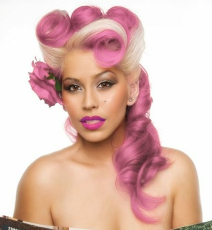 olive-skinned woman with brown eyes, platinum blonde and pink hair, victory rolls and curls, deep pink lipstick and heavy make up