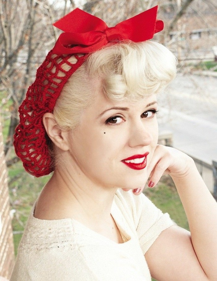 pin up girl hairstyles, woman with black eyes, strong red lipstick and a beauty spot, platinum hair gathered in a red hair net with a bow, curly bangs and white teeth