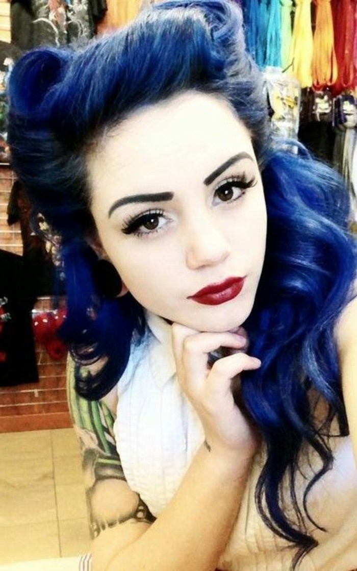 blue-haired pale girl with dark red lipstick and heavy eye make up, fake lashes eyeliner mascara penciled eyebrows, tattoo on arm and white top