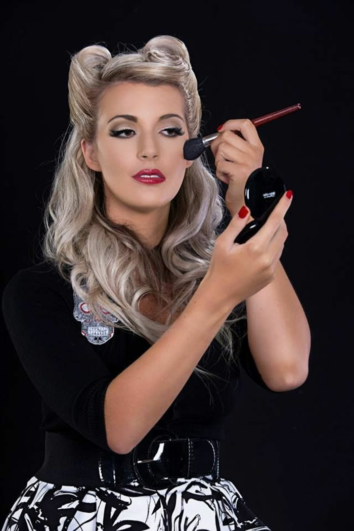 rockabilly hairstyles, platinum blonde woman with victory rolls and curls, wearing heavy make up and bright red lipstick, holding a compact mirror and a brush to her cheek