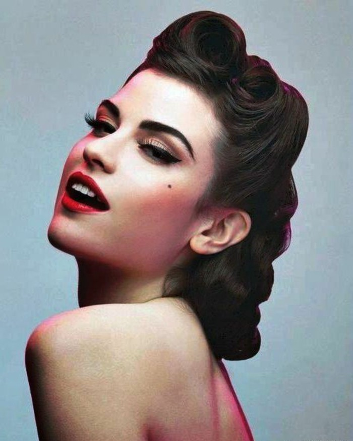 close up of woman with brown 1940's pinup hair, victory rolls and curls, red lipstick white teeth, eyeliner and fake lashes, mascara and a beauty spot, bare shoulders