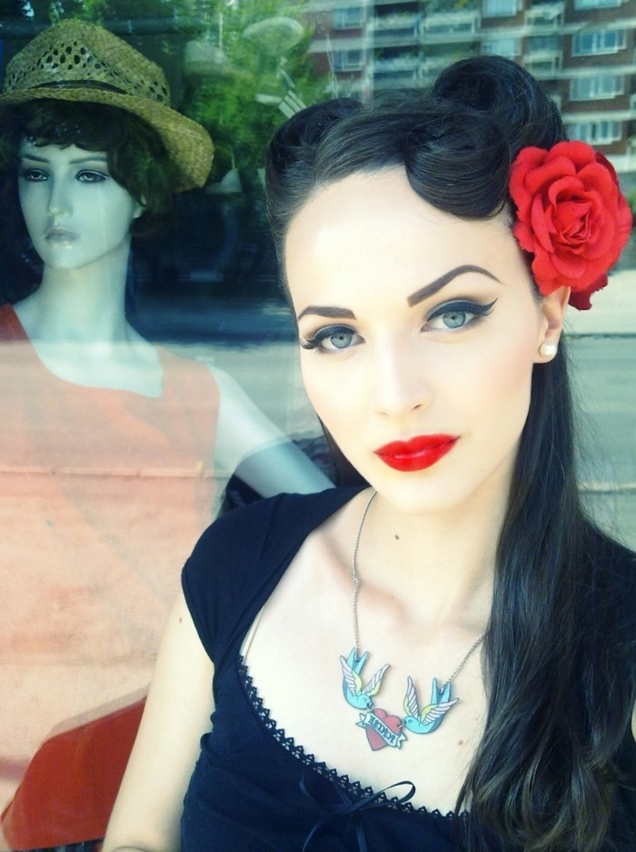 rockabilly hair, woman with very pale skin and heavy make up, bright red lipstick bold black eyeliner and mascara, dyed eyebrows and black hair with victory rolls and a fake red rose